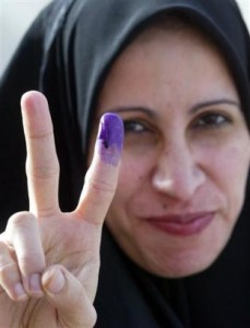 An Iraqi woman flashes victory after voting.